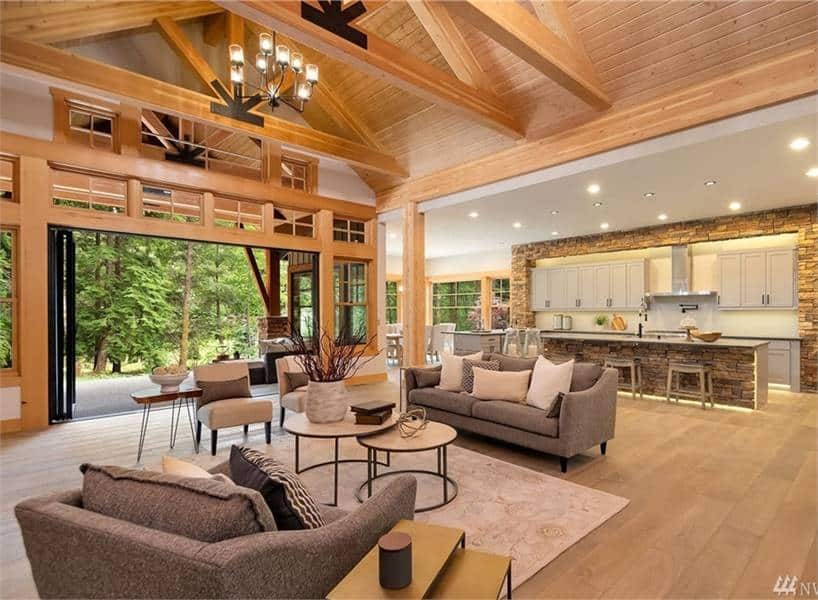 An open layout view showing the living room, kitchen, dining area, and outdoor living accessible via the folding glass doors.