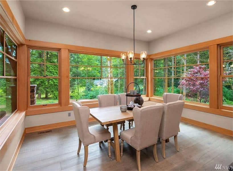 The dining area offers a wooden dining table, gray wingback chairs, and a warm glass chandelier.