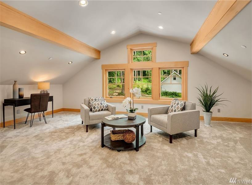 Bonus room with beige armchairs, a round center table, dark wood desk, carpet flooring, and a vaulted ceiling lined with rustic beams.