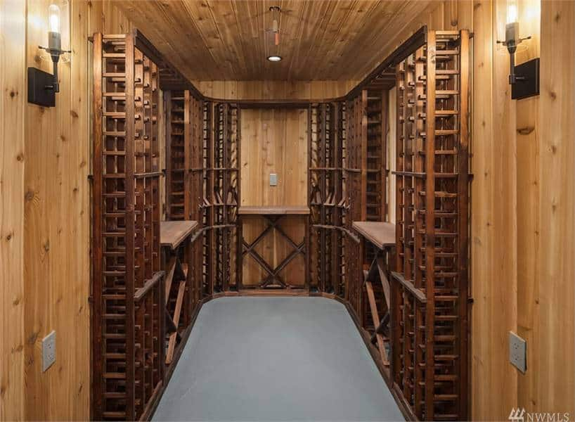The wine cellar is filled with wooden wine racks arranged in columns and crisscross patterns.