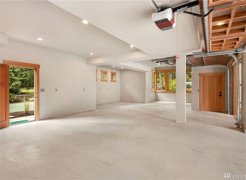 Oversized garage with white walls, concrete flooring, and a storage closet.