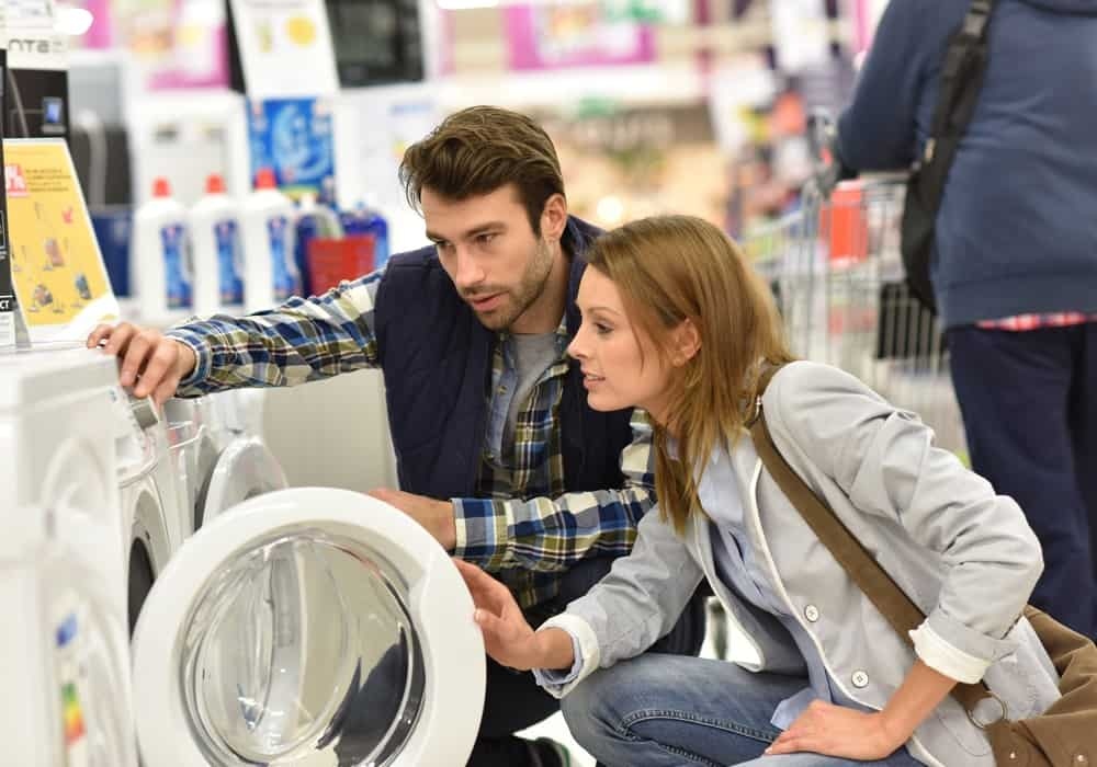 A couple looking at a washing machine for sale at a store.
