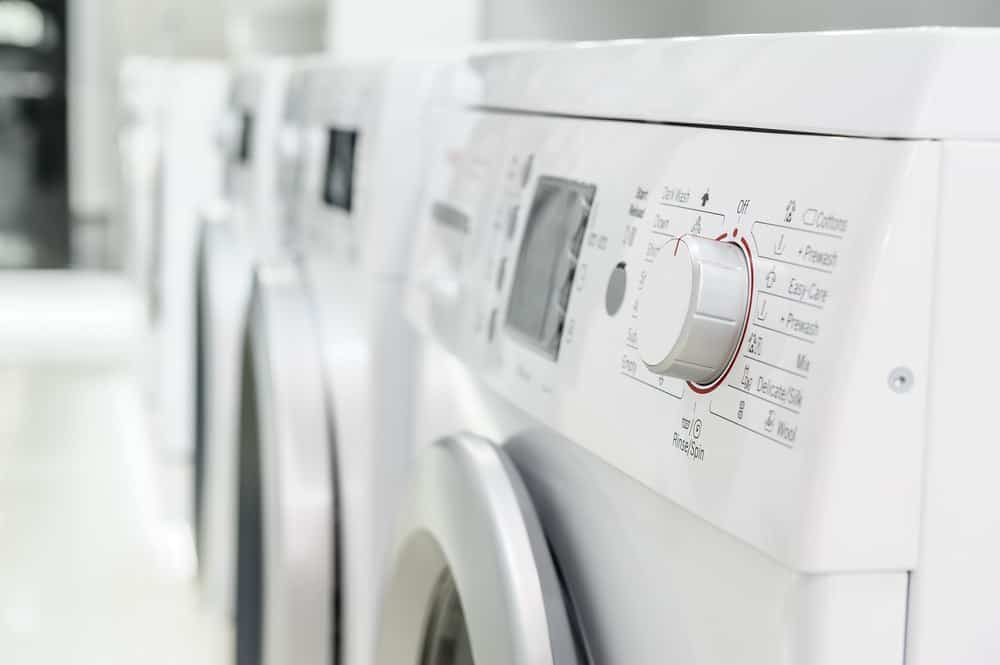 A close look at a row of washing machines for sale at a store.