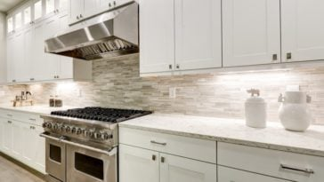 This is a kitchen with white kitchen cabinets lining the walls to make the staonless steel appliances stand out.