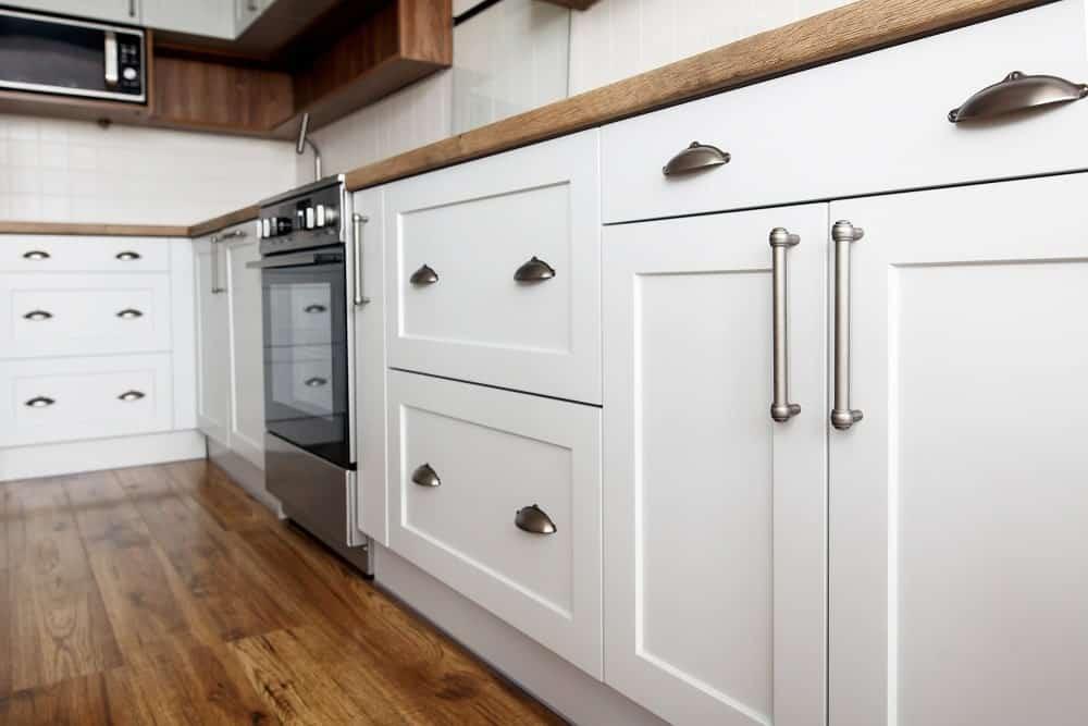 Fırına uygun çelik kulplu mutfağın beyaz çalkalayıcı dolaplarına yakından bir bakış.