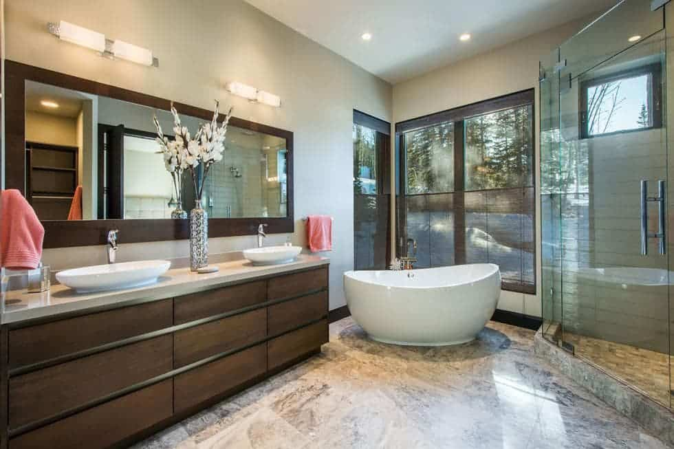 This is the spacious bathroom with a freestanding white bathtub placed at the far corner by the glass wall beside the dark brown vanity and glass-enclosed shower area. Image courtesy of Toptenrealestatedeals.com.