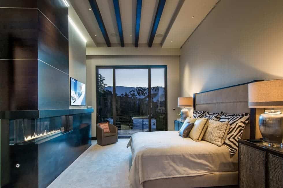 This is the bedroom with a tall beamed ceiling. The large bed has a large cushioned headboard across from the modern fireplace. Image courtesy of Toptenrealestatedeals.com.