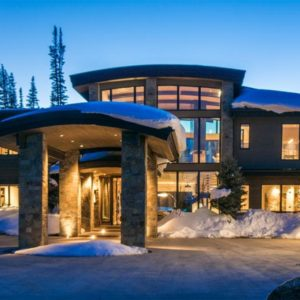 This is a front view of the ski home made of mostly stone exterior walls and large glass walls that showcases the bright interiors and the warm glow of the interior lights. Image courtesy of Toptenrealestatedeals.com.