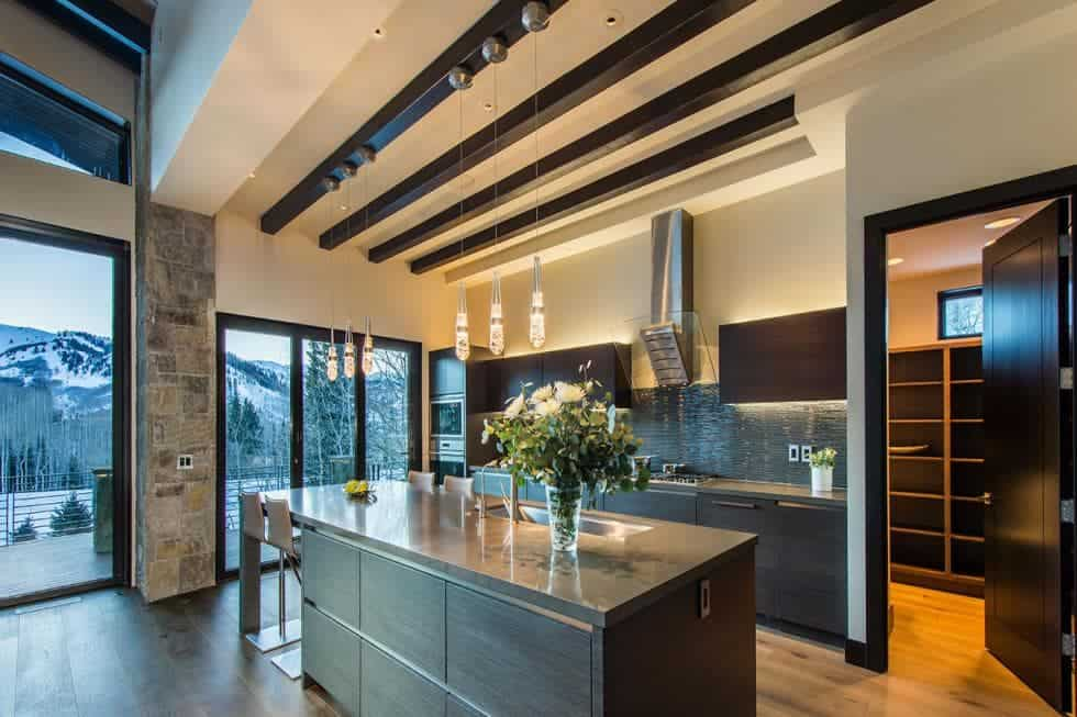 This is the spacious kitchen with a beamed ceiling above the dark cabinetry of the kicthen island to match those lining the walls. Image courtesy of Toptenrealestatedeals.com.