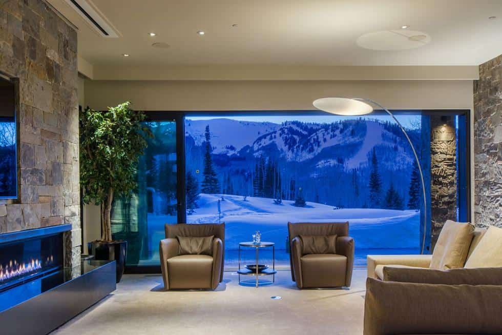 This is the living room on the ground floor with comfortable armchairs and sofa across from the wall-mounted TV above the fireplace. These are then complemented by the large glass wall. Image courtesy of Toptenrealestatedeals.com.