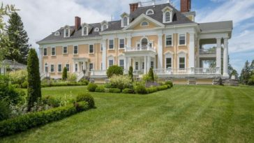 This is a view of the back of the house that has three levels, bright beige exterior walls and tall dormer windows along with chimneys. These are all complemented by the lush landscape of grass lawns and shrubs. Image courtesy of Toptenrealestatedeals.com.