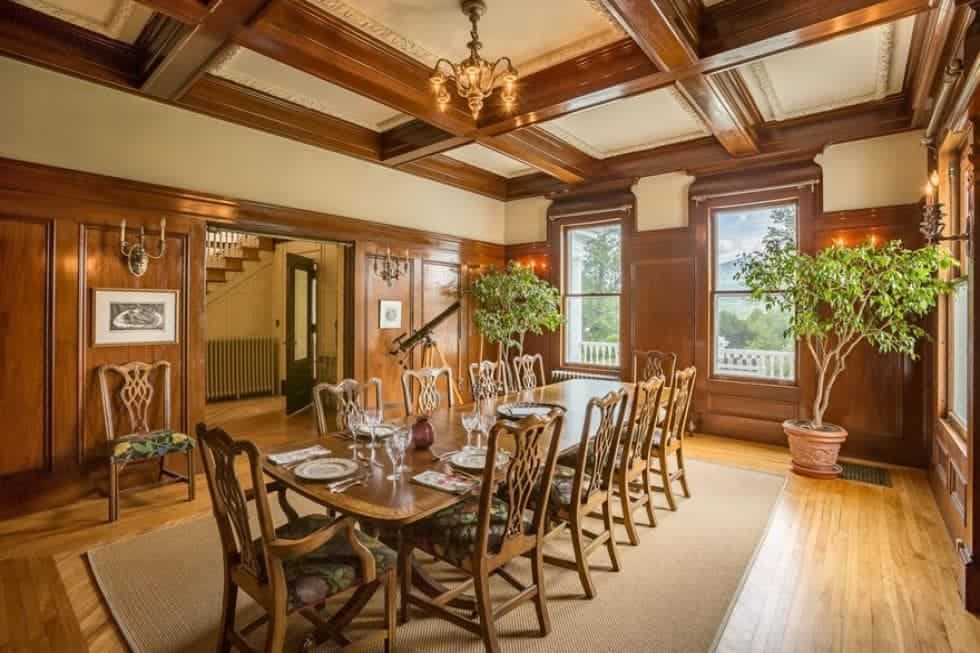 This is the large dining room with a large wooden dining table that matches the wood-paneled walls and coffers of the ceiling. Image courtesy of Toptenrealestatedeals.com.