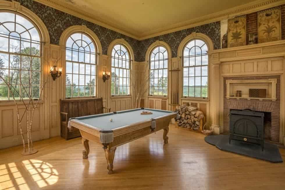 This is the spacious game room with a pool table illuminated by the surrounding arched windows. On the side of the table is a fireplace. Image courtesy of Toptenrealestatedeals.com.