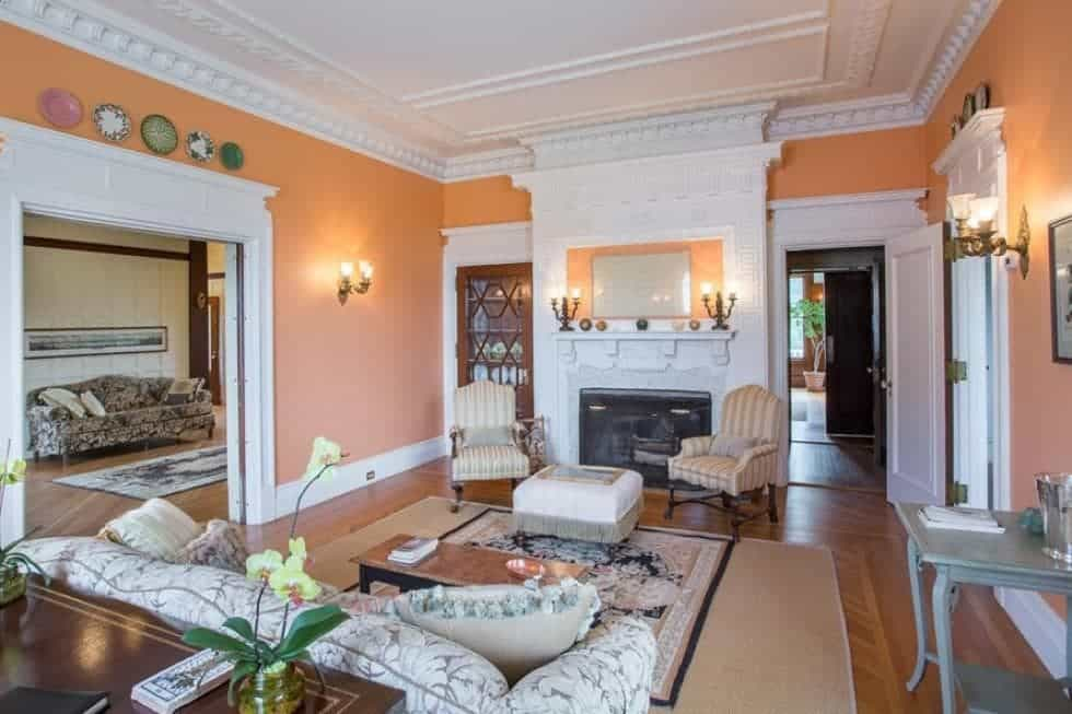 This is the formal living room with a large fireplace across from the patterned sofa that has a white mantle flanked by cushioned chairs. These are then complemented by the pastel tone of the walls. Image courtesy of Toptenrealestatedeals.com.