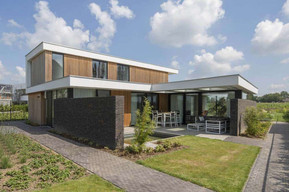 This is a back view of the house that has a small backyard lawn with a small swimming pool by the wooden exterior walls of the house complemented by the glass windows and white frames.