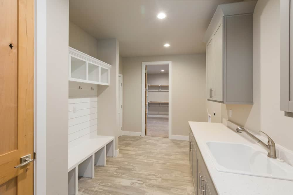 This large room has a white mudroom that stands out against the beige walls and ceiling.
