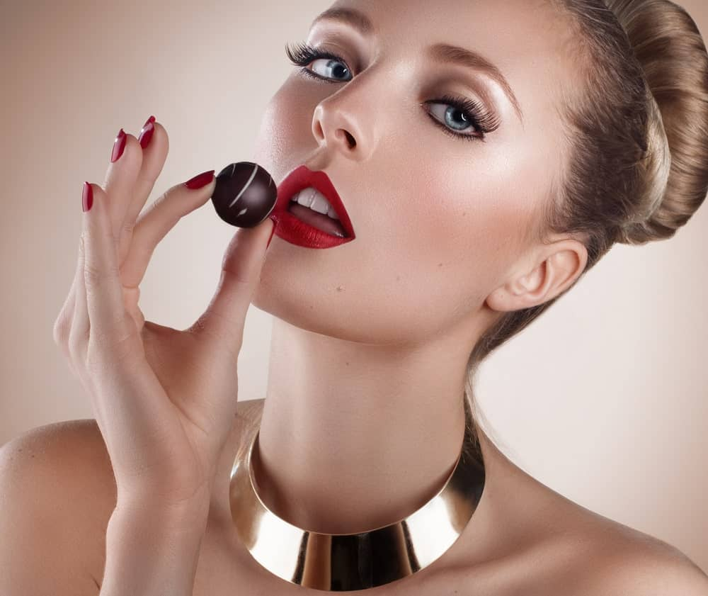 A woman modelling a piece of chocolate.