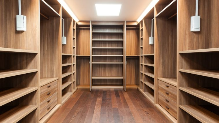 This is a spacious walk-in closet with hardwood flooring to match the brown wooden cabinetry lining the walls.