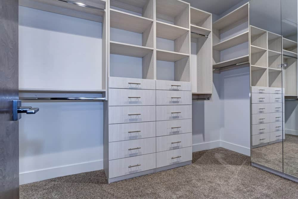 A walk-in closet with white cabinets and shelves complemented by a brown carpeted flooring.