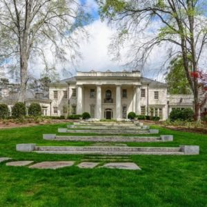 This is the front of the mansion with concrete steps leading to the main entrance of the house that is adorned with bright pillars and white exteriors that stand out against the grass lawn. Image courtesy of Toptenrealestatedeals.com.