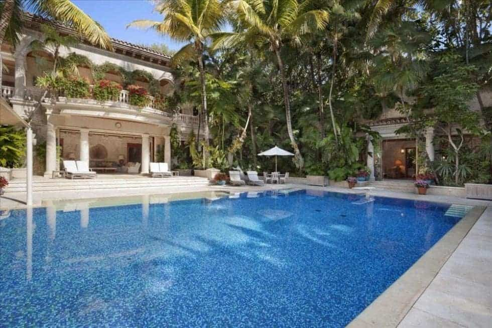 This is a view of the back of the mansion with a large swimming pool and lush landscaping that complements the balcony and pillars of the house exterior. Image courtesy of Toptenrealestatedeals.com.