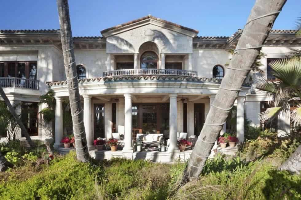This is a look at the covered patio from the landscaping that has tall tropical trees and shrubs. You can also see here the exteriors of the mansion with balconies, columns and windows. The Image courtesy of Toptenrealestatedeals.com.