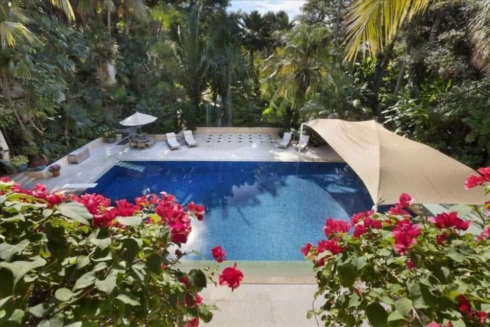 This is the swimming pool as viewed from the vantage of the balcony adorned with flowers. Here you can see the large pool area surrounded by tall trees and shrubs. Image courtesy of Toptenrealestatedeals.com.