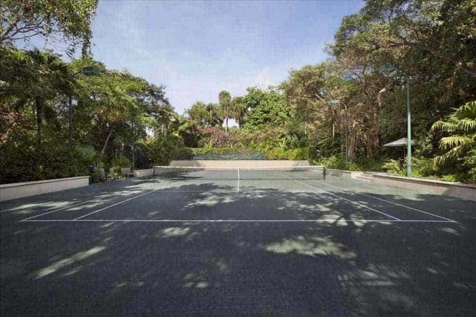 This is the tennis court that is surrounded by tall trees and shrubs to provide privacy and shade. Image courtesy of Toptenrealestatedeals.com.