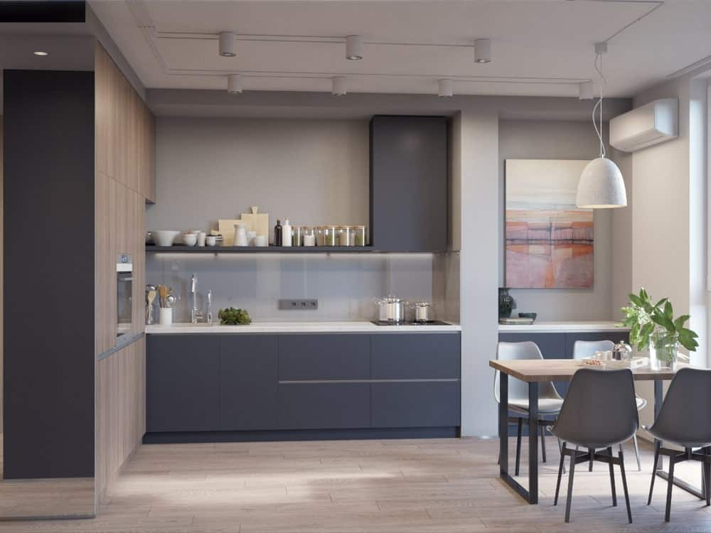 This is a closer look at the kitchen showcasing the gray cabinetry, bright countertops that match the walls and ceiling as well as the edge of the dining area.