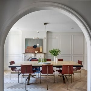 Through a large arched entryway is the formal dining room with a large rectangular dining tab;e surrounded modern chairs and topped with a modern decorative lighting.