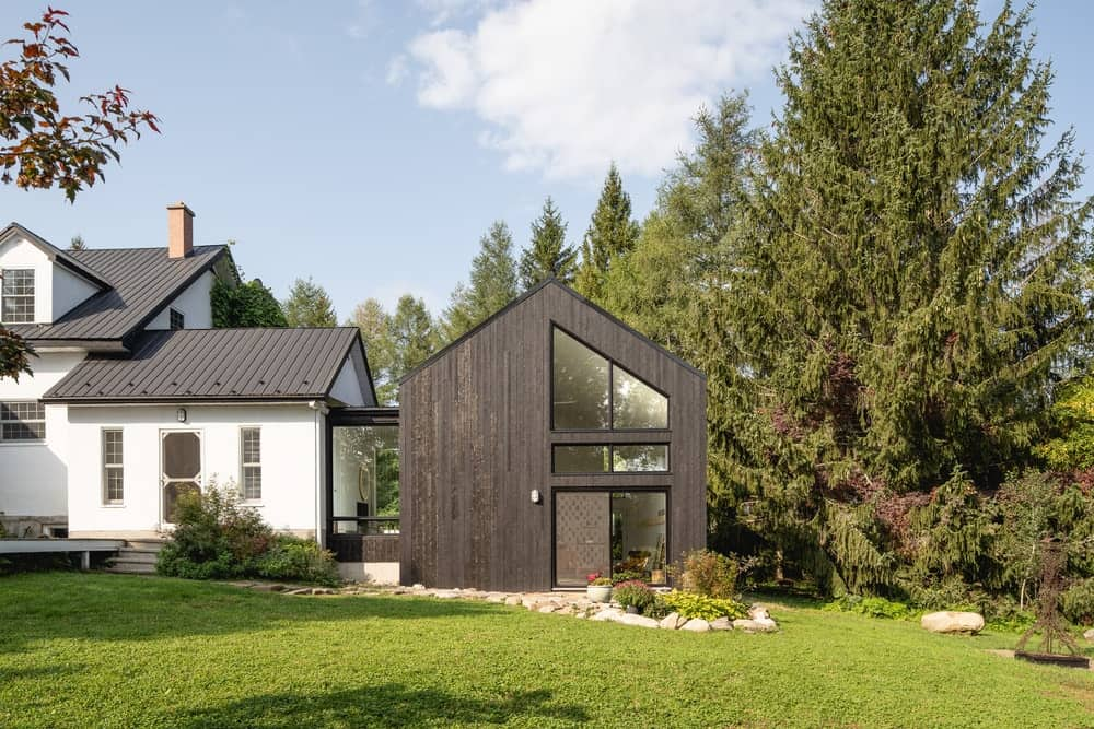 This is a look at the back of the house with a large extension structure that houses the art studio with simple dark tones and glass walls.