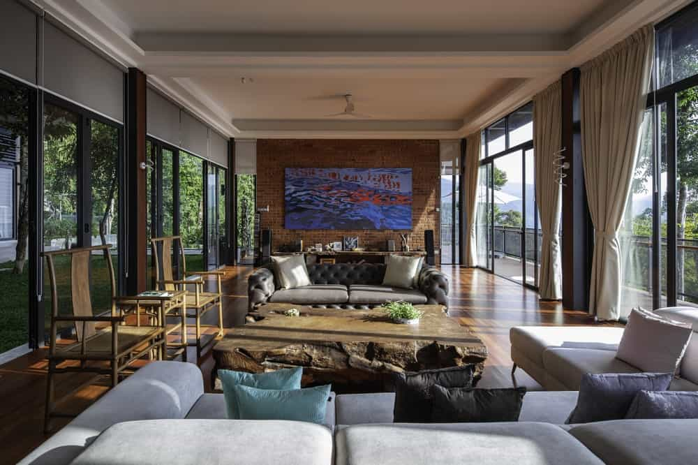 This is the spacious living room on the ground level with sofas, glass walls and a large brick wall on the far side.