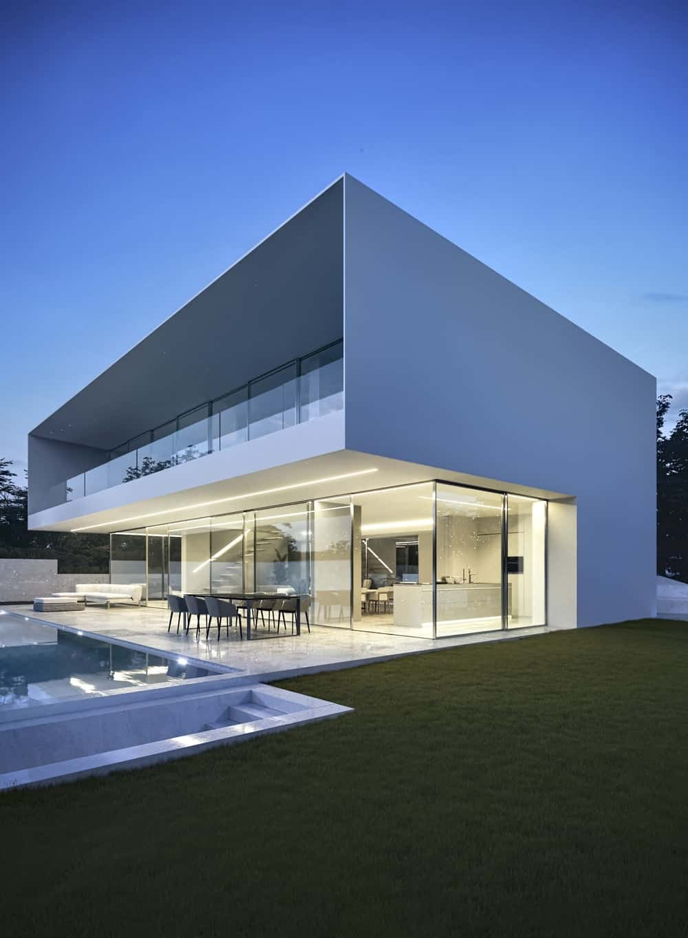 This is a view of the house showcasing the covered patio and the large balcony with glass railings and only the ground level is lit.