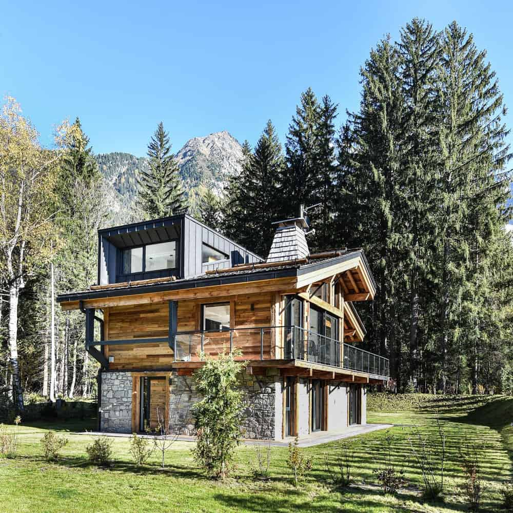 This is a look at the back of the house that has materials of wood, stone and steel along with large glass windows.