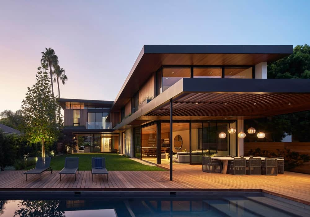This is a look at the back of the house that has abundant glass walls and wooden tones that extend to the wooden deck flooring and walkway leading to the poolside area and outdoor dining area.