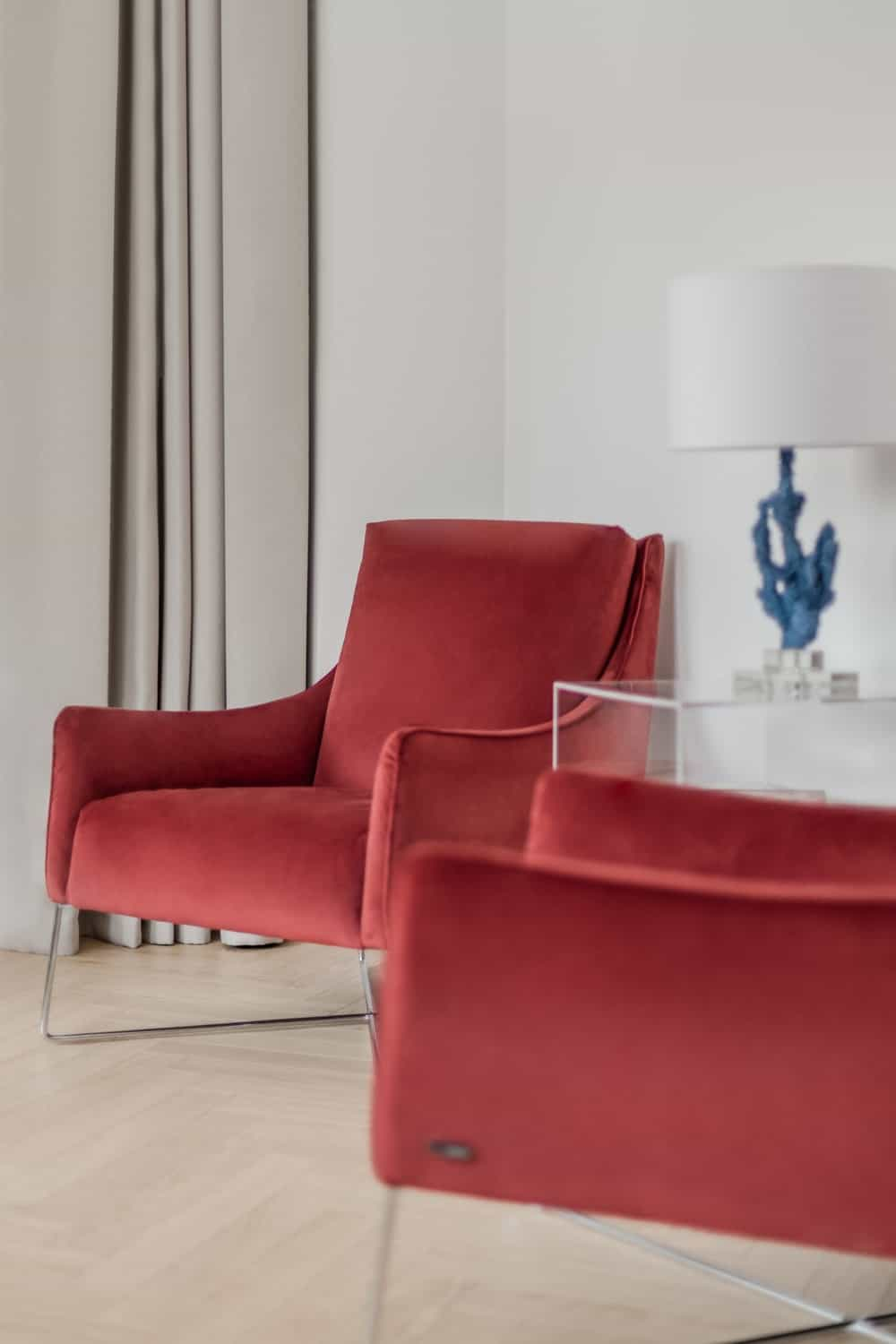 The two cushioned chairs have a red velvet aesthetic that stands out against the light tone of the walls and floor.