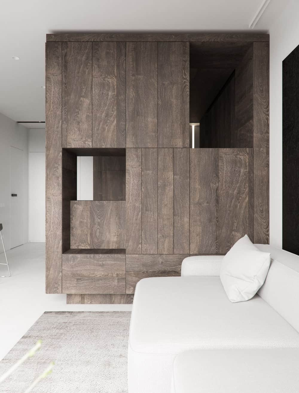This view of the living room showscases more of the large wooden wall made by the structure of the bed. You can see here the cabinets of the wall.