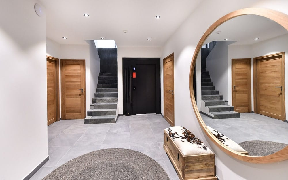 Upon entry of the house, you are welcomed by this foyer that has a large circular mirror above the cushioned bench.