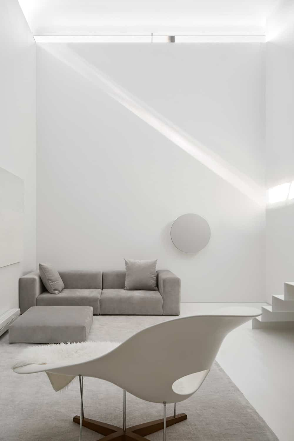 This is the other side of the lounge chair. It has a large gray L-shaped sectional sofa against the white wall by the foot of the modern stairs.