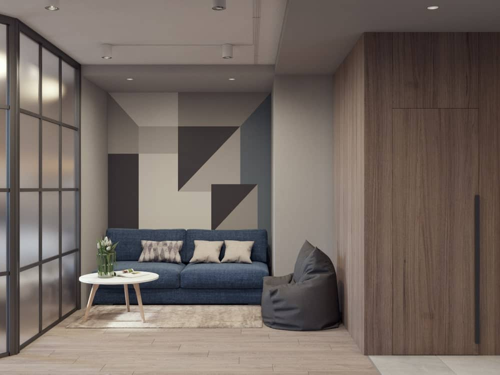 This is the simple living room with a sofa, a white coffee table and a gray bean bag chair adorned by the patterned wall.