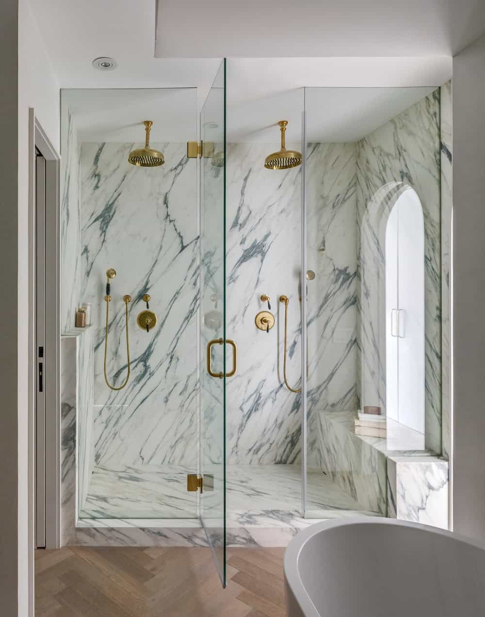 This is a look at the glass-enclosed shower area of the bathroom with white marble walls and floor that makes the bronze fixtures stand out.