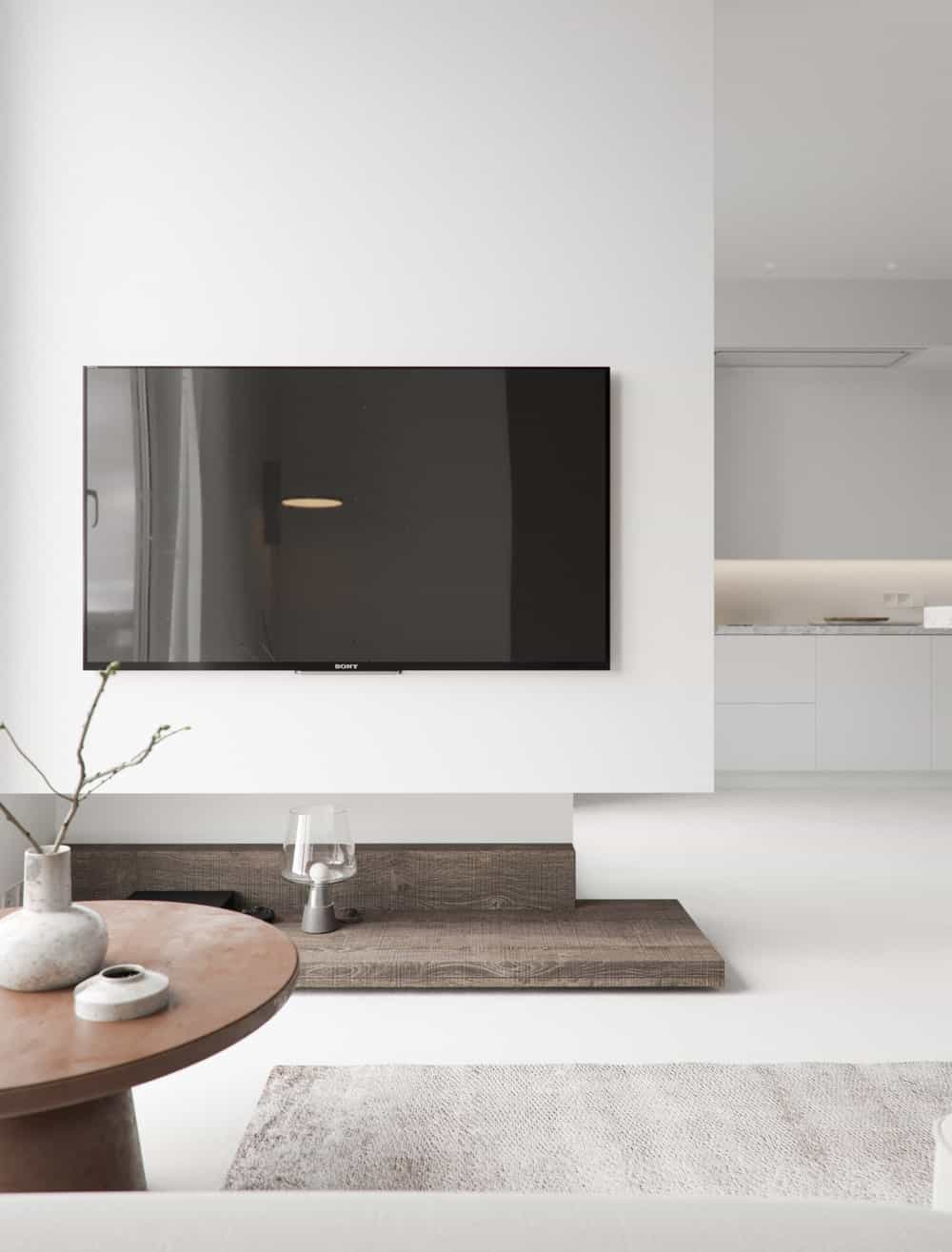 This is the opposite wall of the sectional sofa with a wall-mounted TV and has a view of the kitchen.