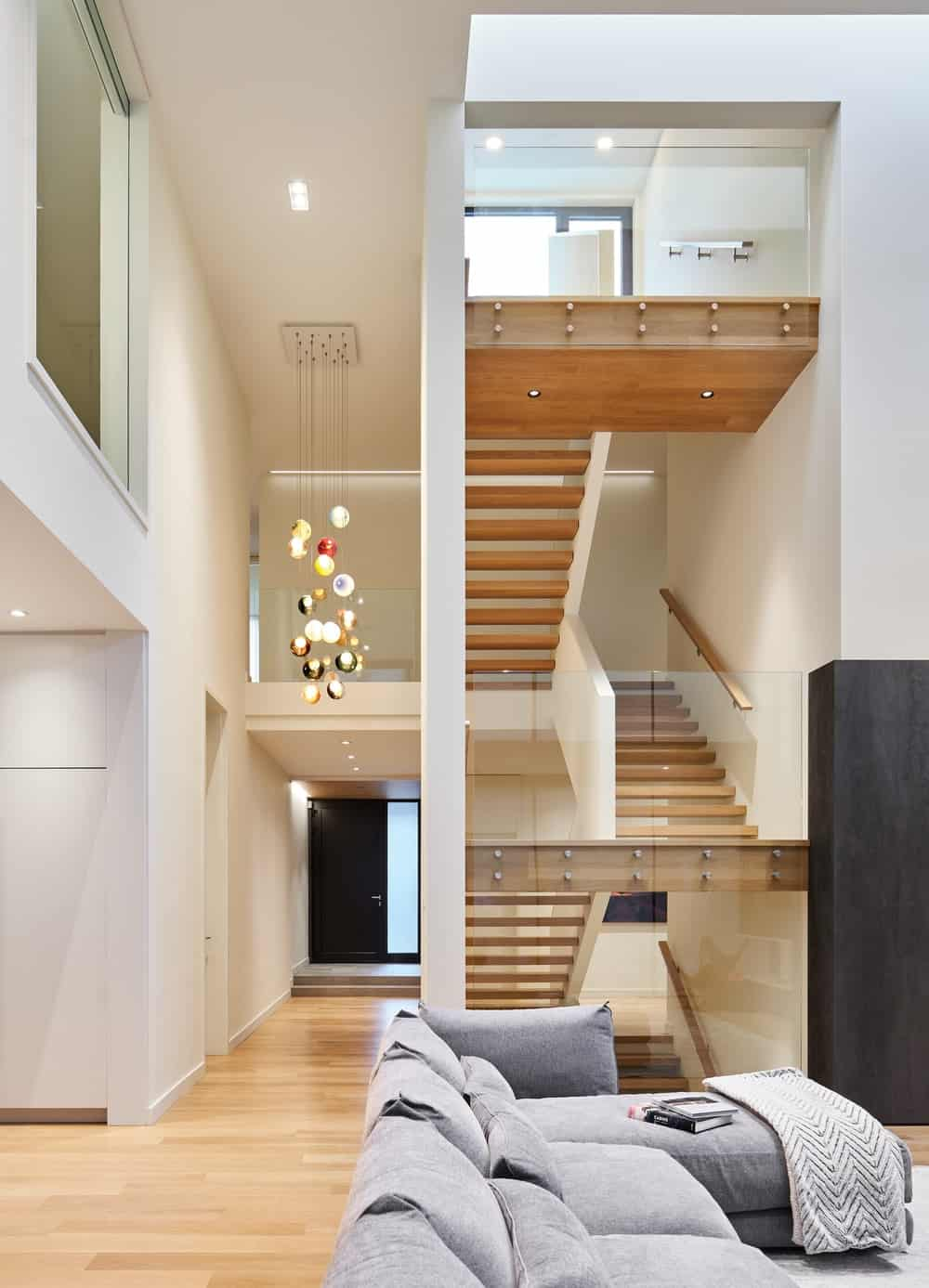 This is a view of the foyer and staircase from the vantage of the living room. You can see here that the foyer is topped with a tall ceiling that has a decorative chandelier.