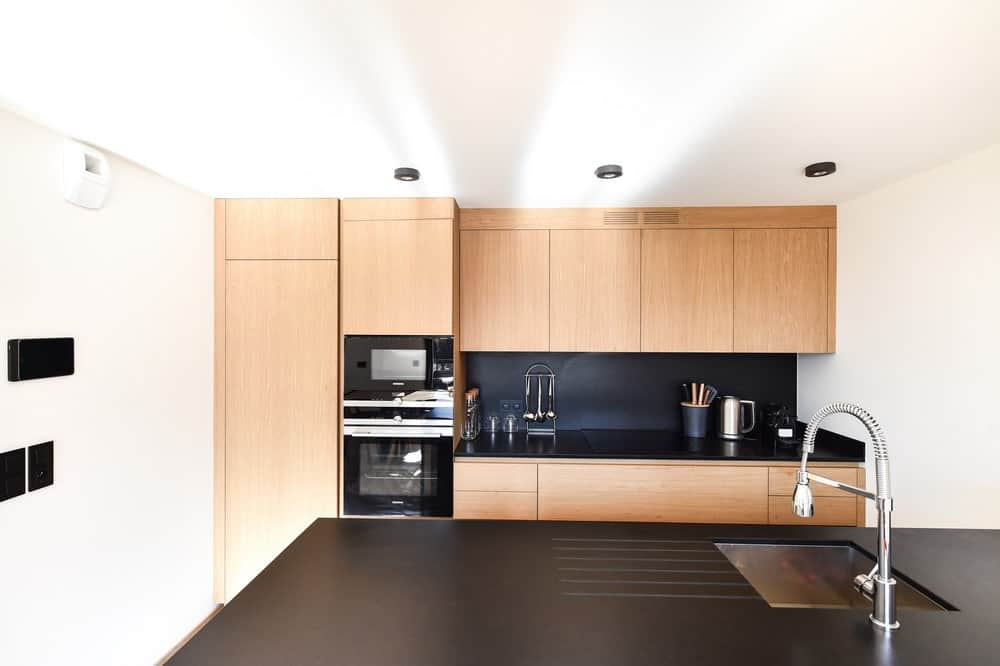The black kitchen peninsula matches with the backsplash of the cabinetry and the modern appliances.