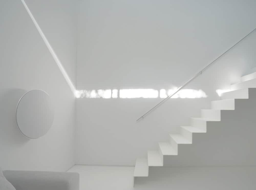 This is the view of the white modern staircase that is adorned with the beam of light coming from the transom window.