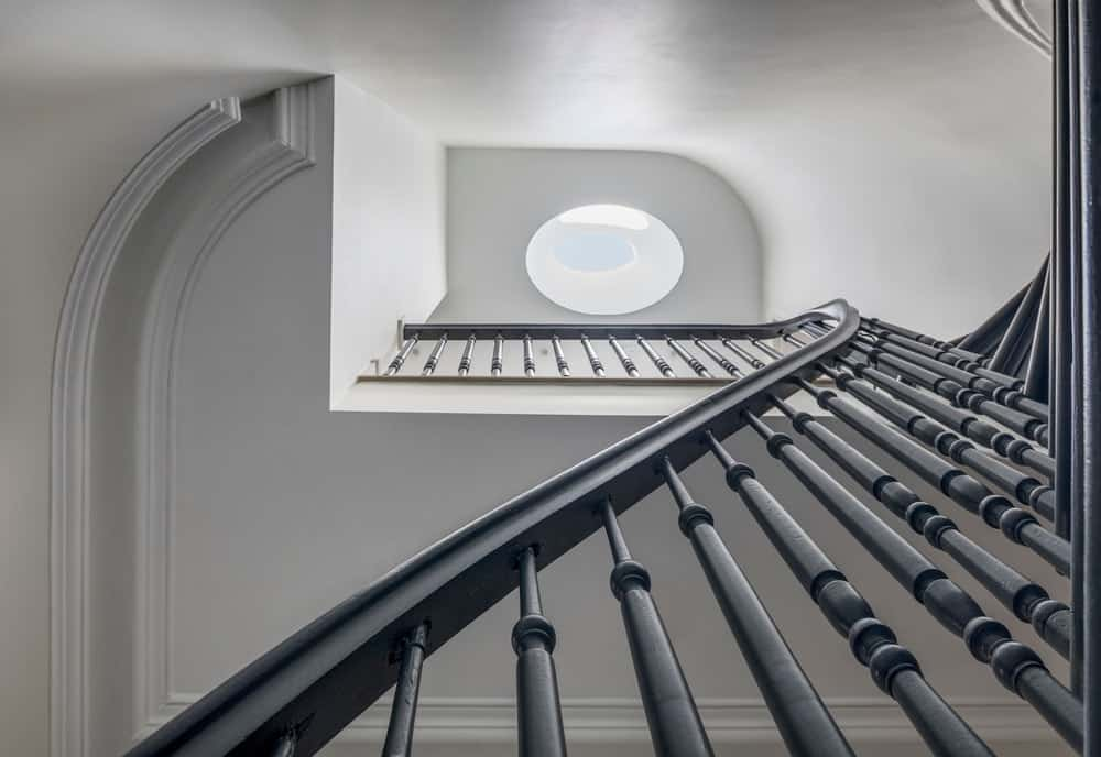 The staircase has a tall ceiling that spans multiple levels and is brightened by the large oblong skylight at the top ceiling.