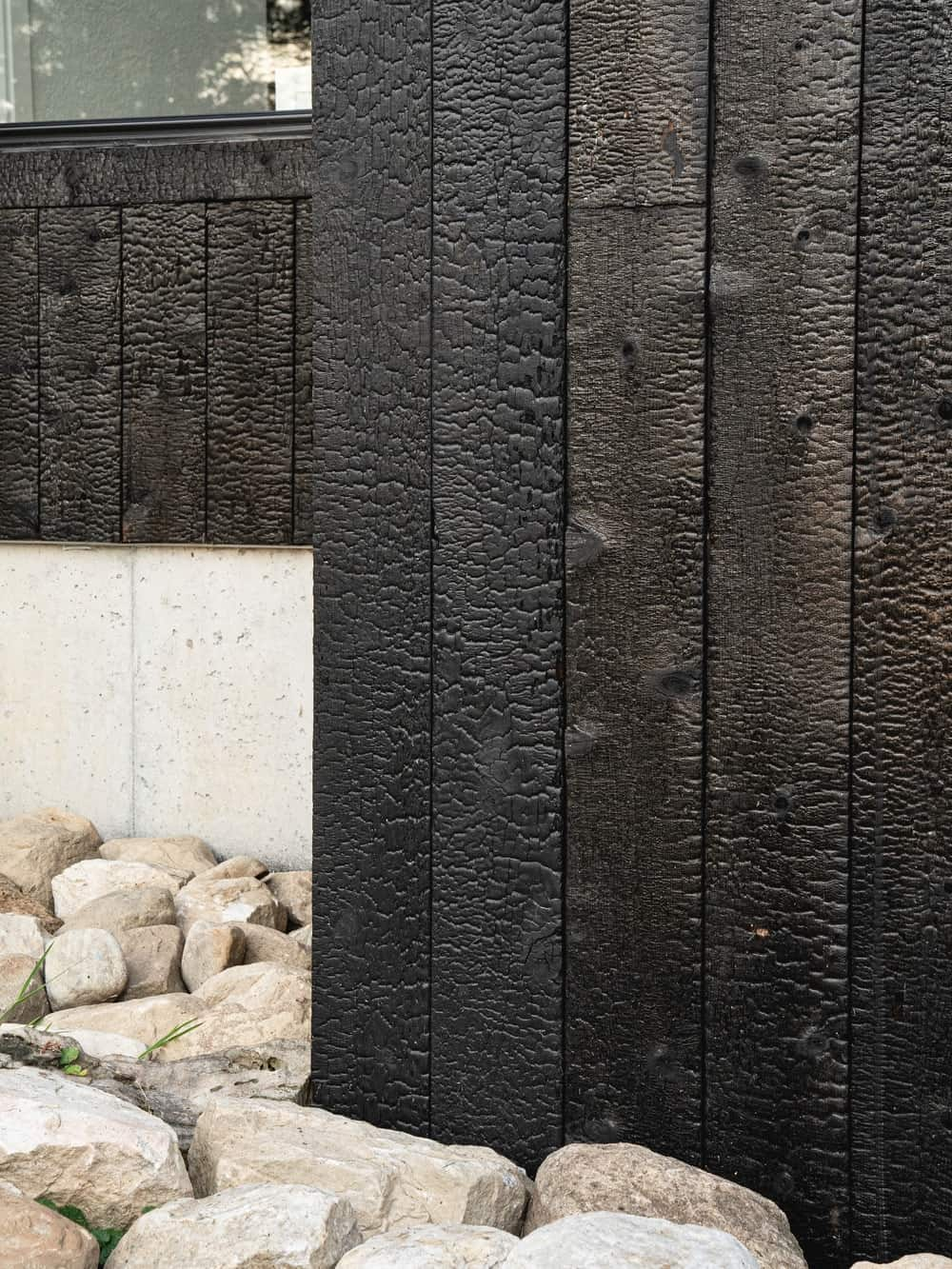 This is a close look at the textured wooden dark exterior walls of the house extension.