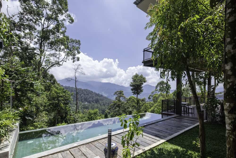 A few steps from the large balcony covered patio is the infinity pool with a wooden walkway on the side.