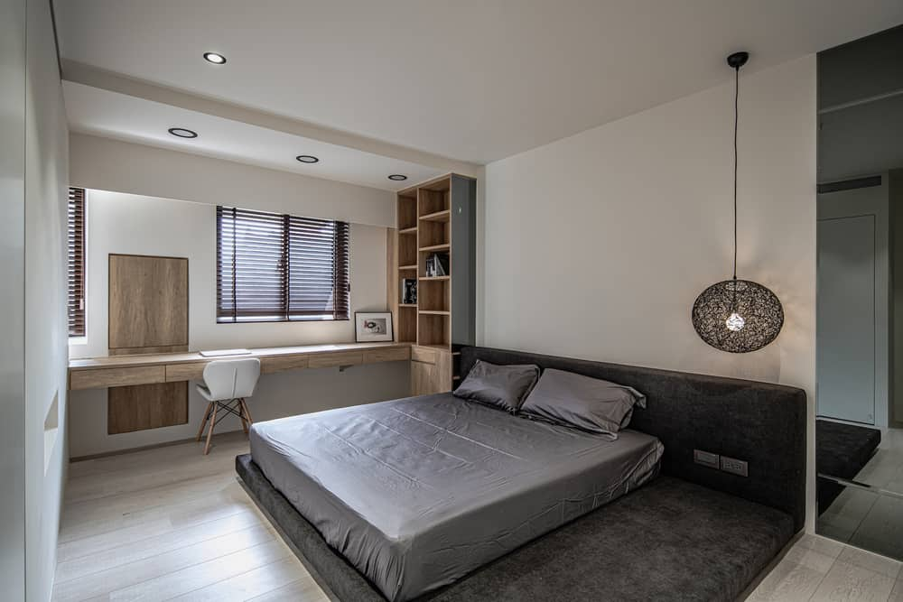 This is the bedroom with a large bed and has a built-in wooden desk on the side paired with a white chair for the study area.
