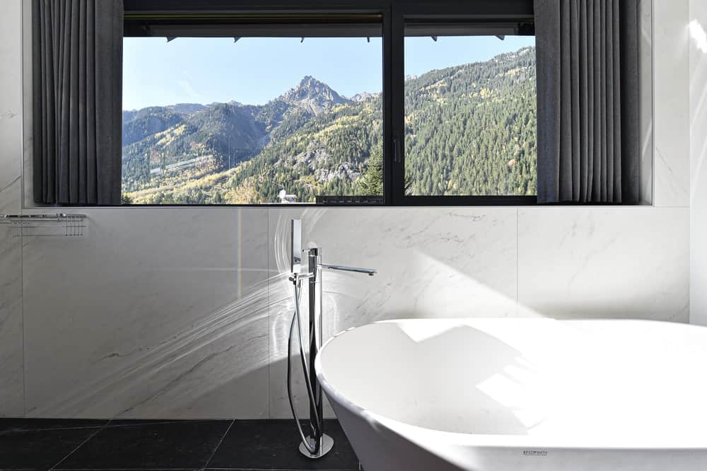 This is a close look at the large freestanding bathtub that is topped with a wide window that showcases the mountain views.